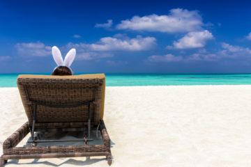 Pasqua 2018: donna indossa orecchie da coniglio pasquale in spiaggia caraibica
